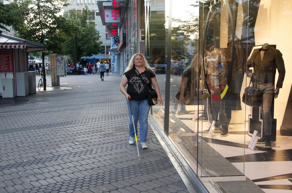 Grit, a blind woman, walks along the window of a shop with the White Cane IO.